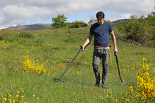 A Man Searching For Buried Ancient Coins And Historic Artefacts With A Metal Detector