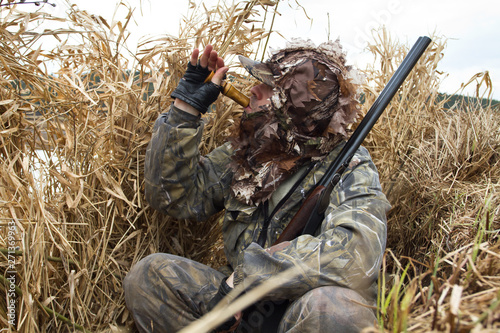 Fotografie, Tablou the hunter hid in the blind of the reeds and lures the ducks