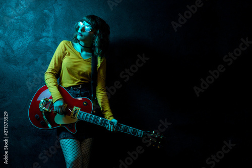 Sensual young hipster woman with curly hair with red guitar in neon lights. Rock musician is playing electrical guitar. 90s style concept. - 271373529