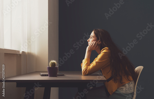 Sad lonely young woman sitting at home Canvas Print