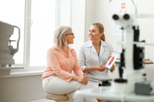 Beaming Long-haired Woman Having Appointment With Older Patient