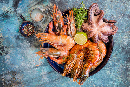 Foto Top view of big plate with grilled shrimps and octopus tentacles decorated with