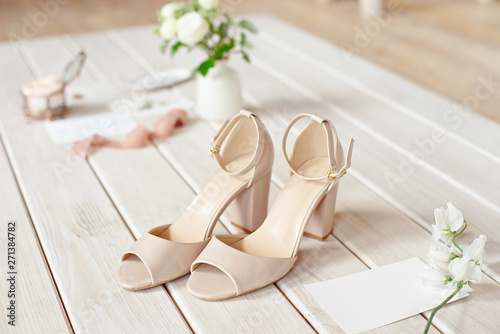 Valokuva Wedding bouquet of white flowers, shoes and wedding rings on a wooden background