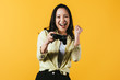 KYIV, UKRAINE - APRIL 16, 2019: happy asian girl playing video game with joystick, isolated on yellow
