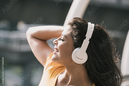 Happy Hispanic woman wearing headphones listening to music - 271386906