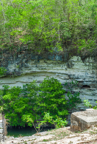 Fotomural Cenote at the bottom of the rocks, taken in the archaeological area of Chichen I