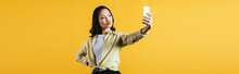 Brunette Asian Woman Taking Selfie On Smartphone Isolated On Yellow