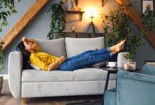 Young Brunette Woman Relaxing On The Couch After A Long Day