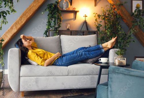 Fototapeta Young brunette woman relaxing on the couch after a long day