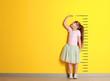 Leinwandbild Motiv Cute little girl measuring height near color wall