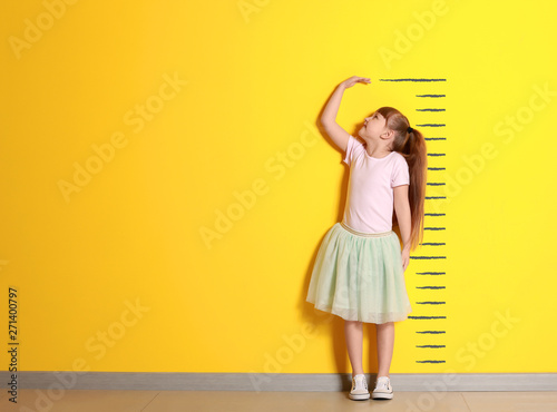 Photo  Cute little girl measuring height near color wall