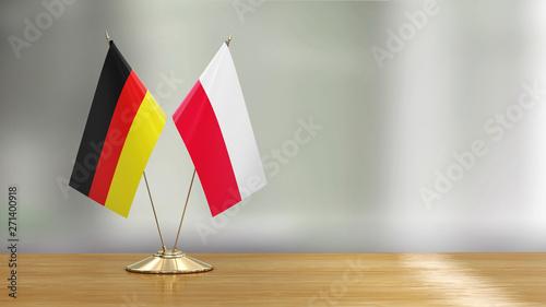 Obraz Polish and German flag pair on a desk over defocused background  - fototapety do salonu