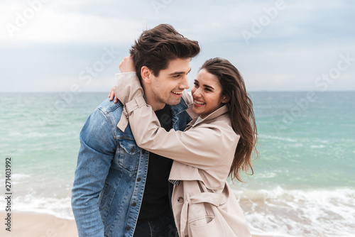 Happy young couple wearing autumn coats