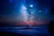 Starry night sky over sea and beach with man silhouette. man standing on sea beach under starry sky.