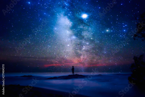 Spoed Foto op Canvas Heelal Starry night sky over sea and beach with man silhouette. man standing on sea beach under starry sky.