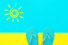 Pair Of Blue Rubber Beach Slippers On Duotone Bright Yellow Cyan Background. Imitation Of Sand And Sea. Hand Drawn Doodle Spiral Sun. Creative Flat Lay. Summer Vacation Travel Relaxation