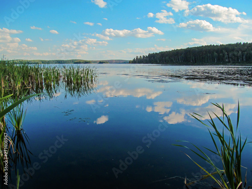 Poster Bleke violet Summer idyllic landscape with lake and sky. Bright day view with blue sky and white clouds and reflection in calm water surface. Lake Chebarkul, South Ural, Russia.