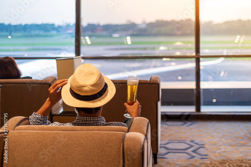 Foto  man traveler with hat holding beer glass and looking to airplane, Asian passenger sitting and relax in modern lounge at international airport terminal