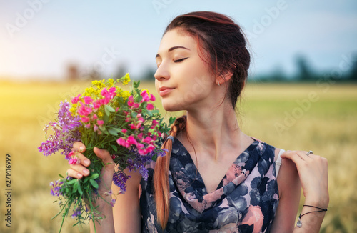 Cute attractive girl with a bouquet of colorful flowers in her hands Canvas Print