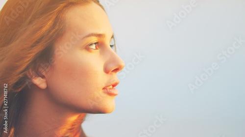 Fotografie, Obraz  Beautiful young woman relaxing and enjoying sun at sunset