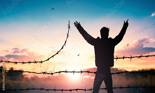 World Refugee Day concept: Man standing on barbed wire at sunset background Canvas Print