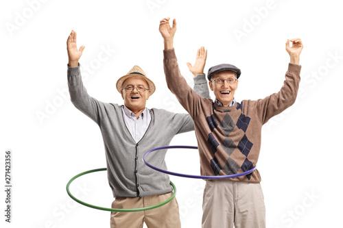 Fotografía  Two cheerful senior men spininng hula hoops