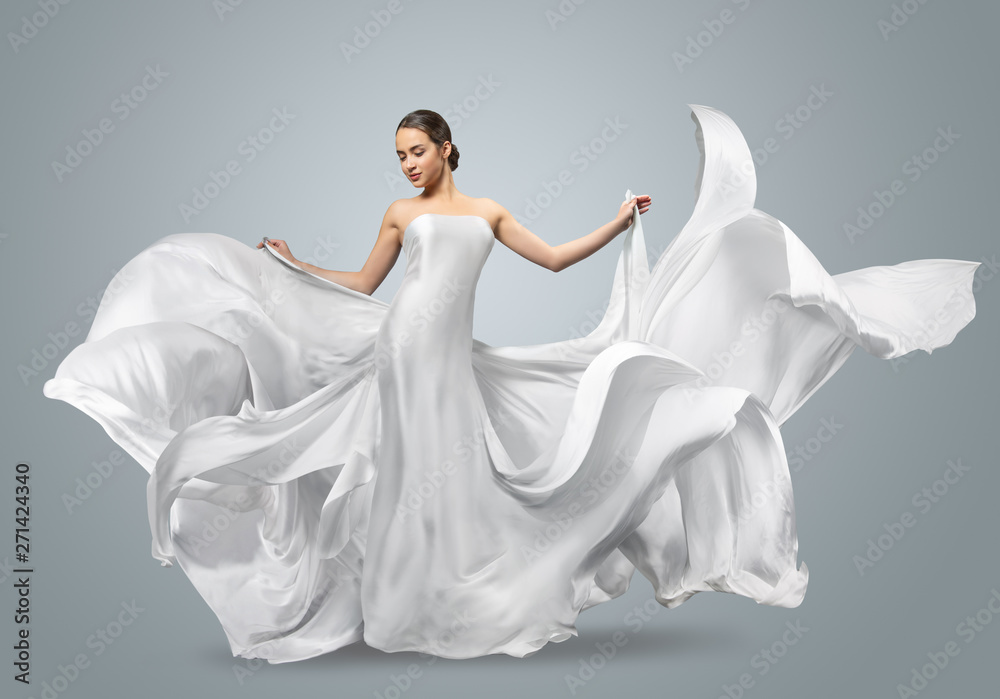 Fototapety, obrazy: Fashion portrait of a beautiful woman in a waving white dress. Light fabric flies in the wind.