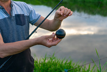 Angler Holding A Device To Measure The Depth Of Water In The River. River In The Background. Close-up On The Ball - The Meter Of The Bottom Of The Water Reservoir. The Water Reflects Clouds And Sky.