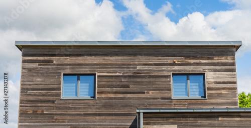 Modernes Wohnhaus mit Fassade aus Holz und Flachdach aus Blech - Modern residential house with wooden façade and flat roof made of sheet metal