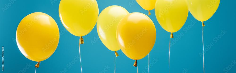 Fototapeta bright party yellow balloons on blue background, panoramic shot