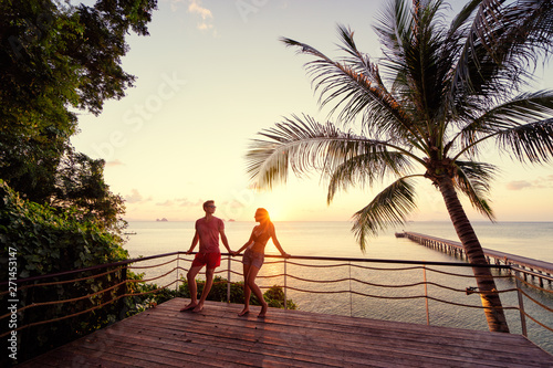 Poster Lieu connus d Asie Romantic dating. Honey moon on tropical shore. Young loving couple standing together on terrace enjoying beautiful sea view.