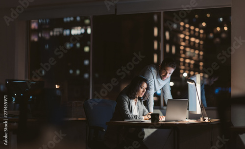 Young business colleagues working overtime together at an office desk - fototapety na wymiar