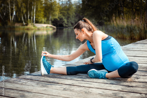 fototapeta na drzwi i meble Pregnancy exercise, pregnant woman stretching outdoor