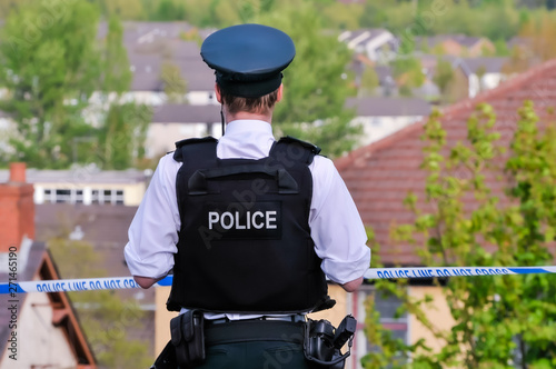 A police officer stands guard at a police cordon point during a security event Fototapeta