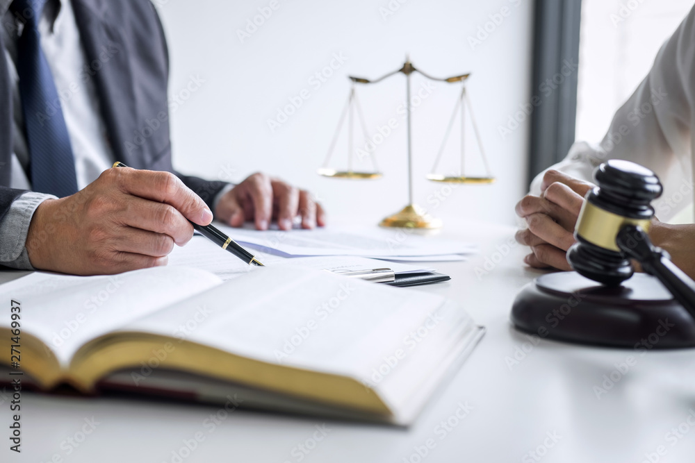 Fototapeta Consultation and conference of professional businesswoman and Male lawyers working and discussion having at law firm in office. Concepts of law, Judge gavel with scales of justice