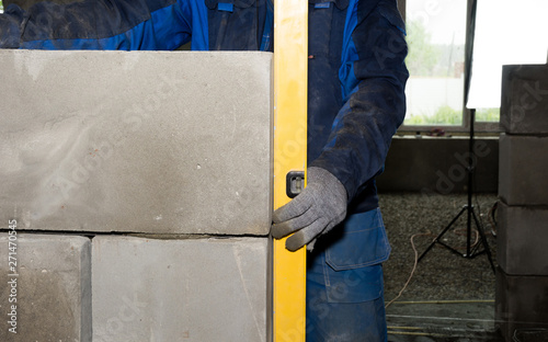 Fototapeta Industrial worker building exterior walls, using level for laying blocks in cement. Detail of worker with tools obraz na płótnie