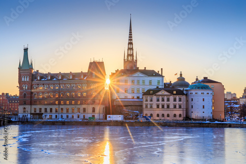 Photo sur Aluminium Stockholm Riddarholmen - part of the historical Old Town (Gamla Stan) in Stockholm, Sweden, at sunrise in winter. Sun star is directly behind the islet and ice is formed on the frozen lake water surrounding it.