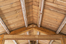 Background Of Wooden Vaulted Ceiling With Bearing Beams And Rafters Close Up