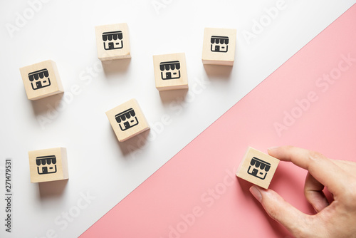 Photo Woman hand choose wood blog with franchise icon on pink background