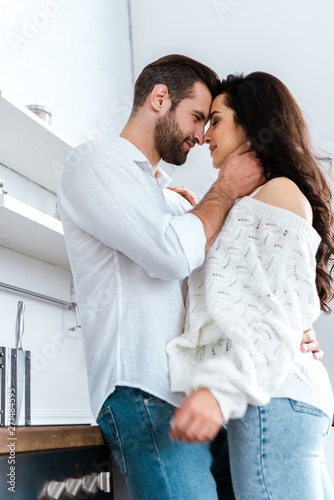 Fotografija low angle view of lovely gently couple embracing at kitchen