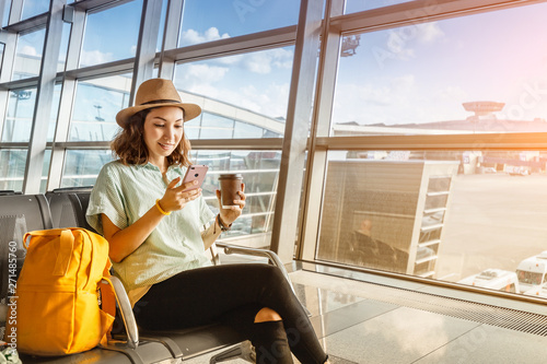 Obraz Asian girl waiting for departure at the airport on your vacation. Uses a smartphone and drinks coffee - fototapety do salonu