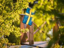 Swedish Flag On A Floating Dock In Summer Sunset Light In Sweden.