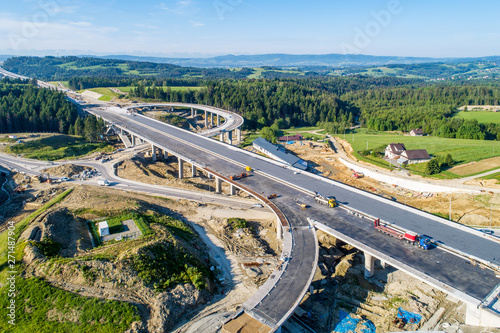 Obraz New highway under construction in Poland on national road no 7, E77, called Zakopianka.  Overpass crossroad with traffic circles and viaducts near Naprawa village. Aerial view in June 2019 - fototapety do salonu