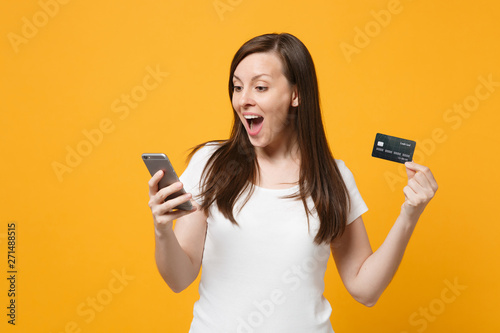 Fototapeta Excited young woman in white casual clothes keeping mouth open, using mobile phone, holding credit bank card isolated on bright yellow orange background. People lifestyle concept. Mock up copy space. obraz na płótnie