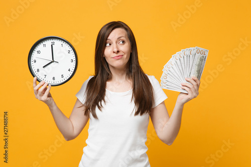 Fotografie, Obraz  Portrait of puzzled young woman in white casual clothes holding round clock, fan of cash money in dollar banknotes isolated on yellow orange background