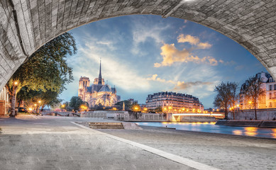 Notre Dame de Paris view from the Seine river with no people at sunset. View from under the bridge of the cathedral in Paris, France.