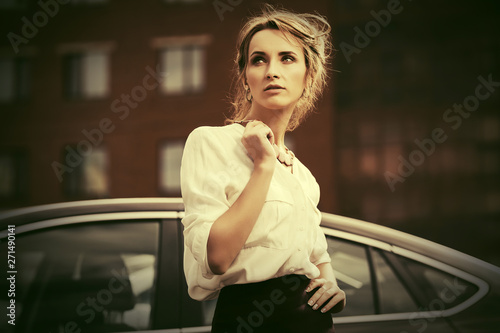 obraz dibond Young fashion business woman in white shirt next to her car