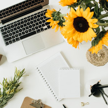 Flatlay Of Home Office Desk Workspace With Laptop, Notebook, Yellow Sunflowers Bouquet On White Background. Top View Freelancer / Blogger Summer Floral Work Concept.