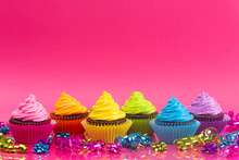 Rainbow Colored Frosted Chocolate Cupcakes On A Bright Pink Background