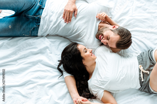 Fototapeta top view of happy couple lying together in bed and looking at each other obraz